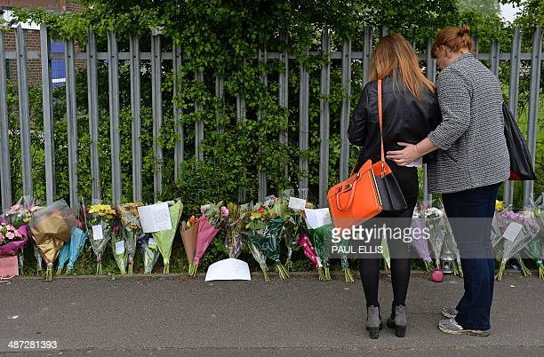 Woman and child look at floral tributes left at Corpus Christi Catholic College in Leeds, northern England, on April 29 following the fatal stabbing...