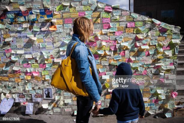 A woman and child look at messages of support and condolence on a wall on the south end of London Bridge following the June 3rd attacks on June 10...