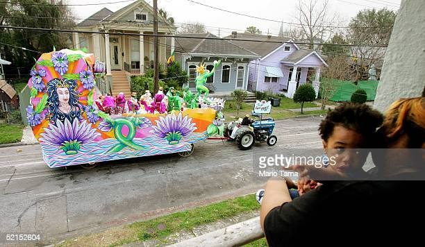 A woman and child look on as a float passes during the historic Proteus parade founded in 1882 during Mardi Gras festivites February 7 2005 in New...