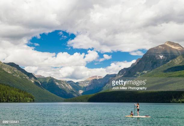 Woman And Child Paddleboarding Across Bowman Lake