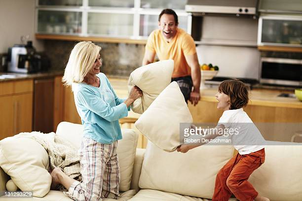 A woman and child pillow fight on a couch.