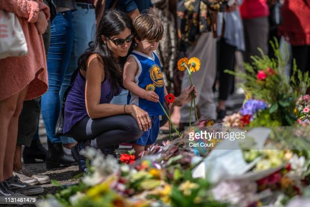 Woman and child place flowers among other tributes by the botanical gardens on March 19, 2019 in Christchurch, New Zealand. 50 people were killed,...