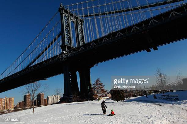 A woman and child play near the Manhattan Bridge on the waterfront after a snowstorm January 21 2011 in the Brooklyn borough of New York City Another...