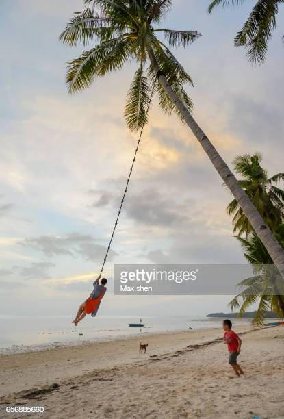 woman and child playing on the rope swing at the beach of siquijor - cebu stock photos and pictures