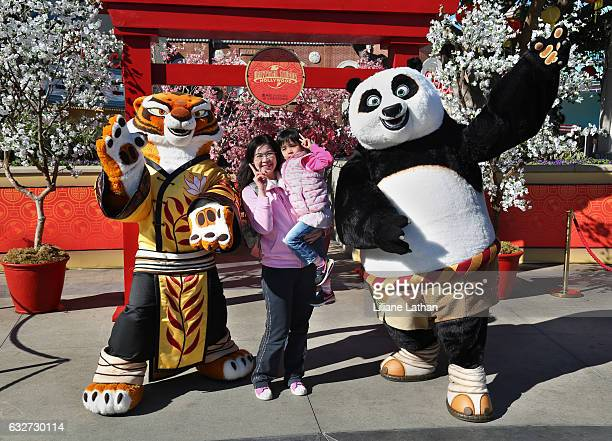Woman and child pose with Tigress and Po from the 'Kung Fu Panda' film series at Universal Studios Hollywood on January 25 2017 in Universal City...