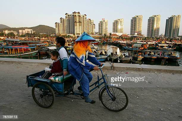 A woman and child rides in the back of a tricycle in a small fishing village near Sanya Harbor on November 30 2007 in Sanya of Hainan province China...