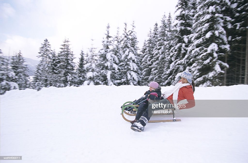 Woman and child riding on sledge : Stockfoto