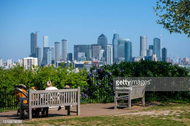 Woman and child sit on a park bench overlooking a view of the Canary Wharf business, financial and shopping district of London, U.K., on Tuesday,...