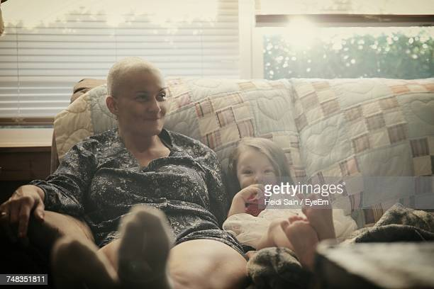 woman and child sitting on sofa at home - cancer stock photos and pictures