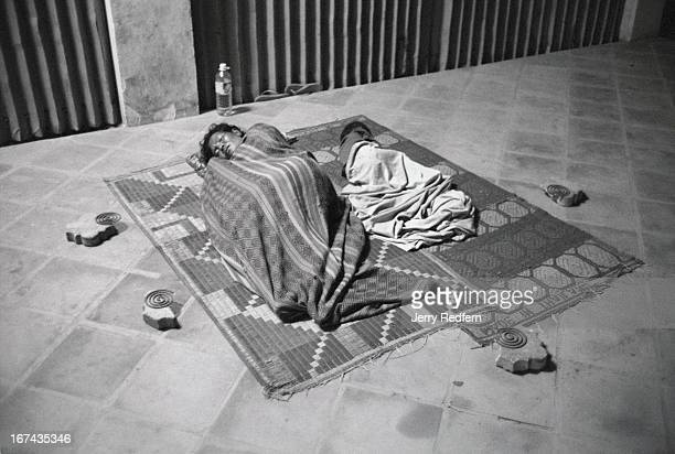 A woman and child sleep on a mat surrounded by mosquito coils on the sidewalk in front of the provincial social welfare office in the middle of town...