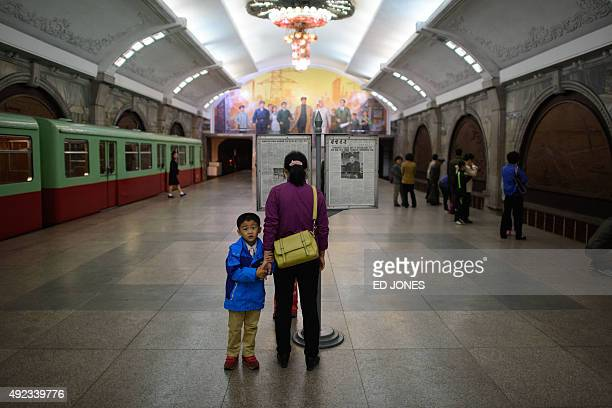 A woman and child stand in a Pyongyang subway station on October 12 2015 North Korea wrapped up the 70th birthday party for its ruling Worker's Party...
