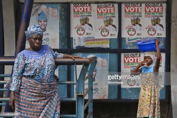 A woman and child stand near campaign poster of Atiku Abubakar candidate of the main opposition People's Democratic Party in Lagos Nigeria Saturday...