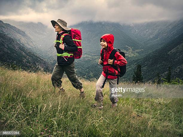 woman and child trekking in the mountains - leanincollection stock pictures, royalty-free photos & images