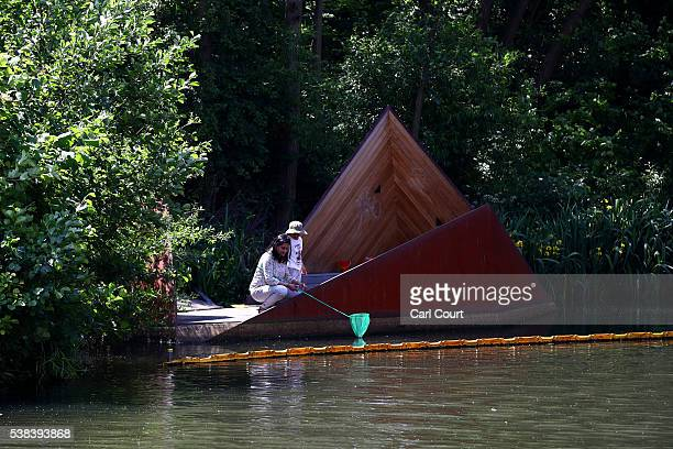 A woman and child use a net to scoop for tadpoles and waterborne arthropods on June 6 2016 in London England Temperatures reached a high of 24C in...