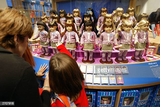 A woman and child view dolls for sale at a press preview for the opening of American Girl Place New York November 7 2003 in New York City The...