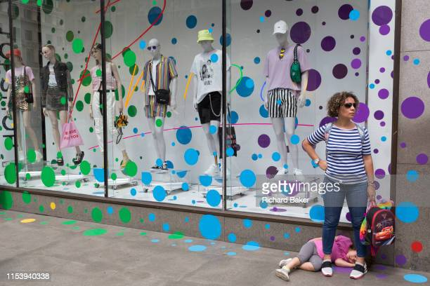 A woman and child wait outside the spottedtheme window display of Topshop on Oxford Street on 2nd July 2019 in London England