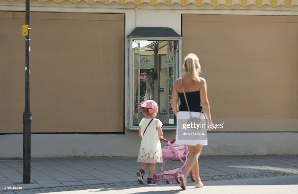 A woman and child walk past a shuttered shop one day before a planned march by protesters in the city center and two days before the summit of G7 leaders on June 5, 2015 in Garmisch-Partenkirchen, Germany. G7 leaders will meet at nearby Schloss Elmau on June 7-8 and at least 17,000 police members are on hand to safeguard security at the summit.