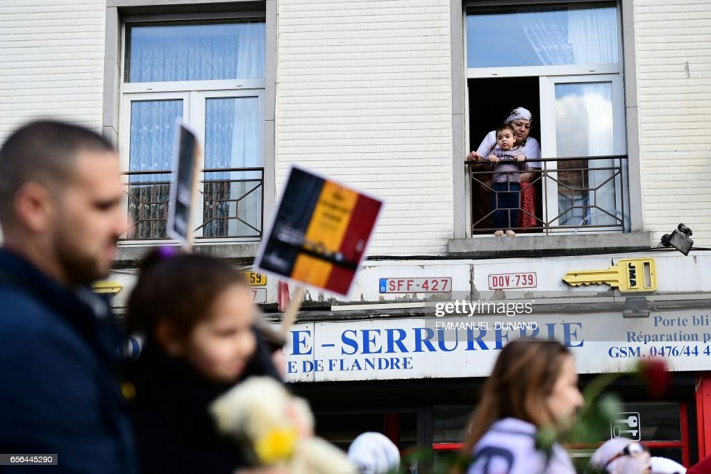 A woman and child watch as people take part in a commemorative march as Belgium marks the first anniversary of the twin Brussels attacks by Islamic extremists on March 22, 2017 in Brussels. Belgium marks the first anniversary of the Islamic State bombings in Brussels, one at the airport and the other in the metro, in which 32 people were killed and more than 320 wounded with ceremonies showing that the heart of Europe stands defiant. / AFP PHOTO / Emmanuel DUNAND