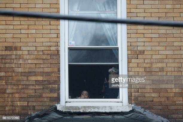 A woman and child watch from a window as Chicago Police officers investigate the scene where four people were shot and killed at a restaurant in the...
