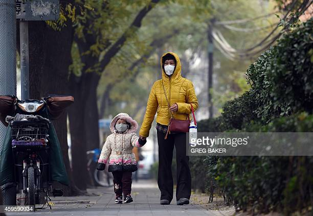 A woman and child wear masks as they walk on a polluted day in Beijing on November 26 2014 China said on November 25 that developed countries must do...