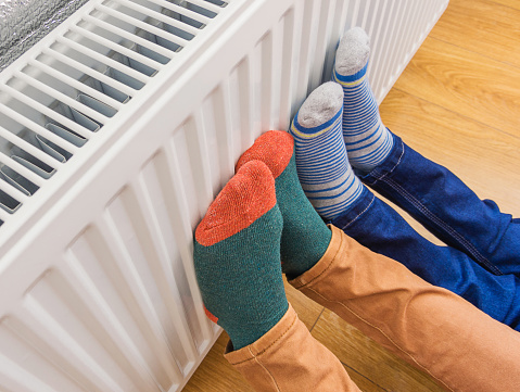 Woman and child wearing colorful pair of woolly socks warming cold feet in front of heating radiator in winter time. Electric or gas heater at home. 1051686128