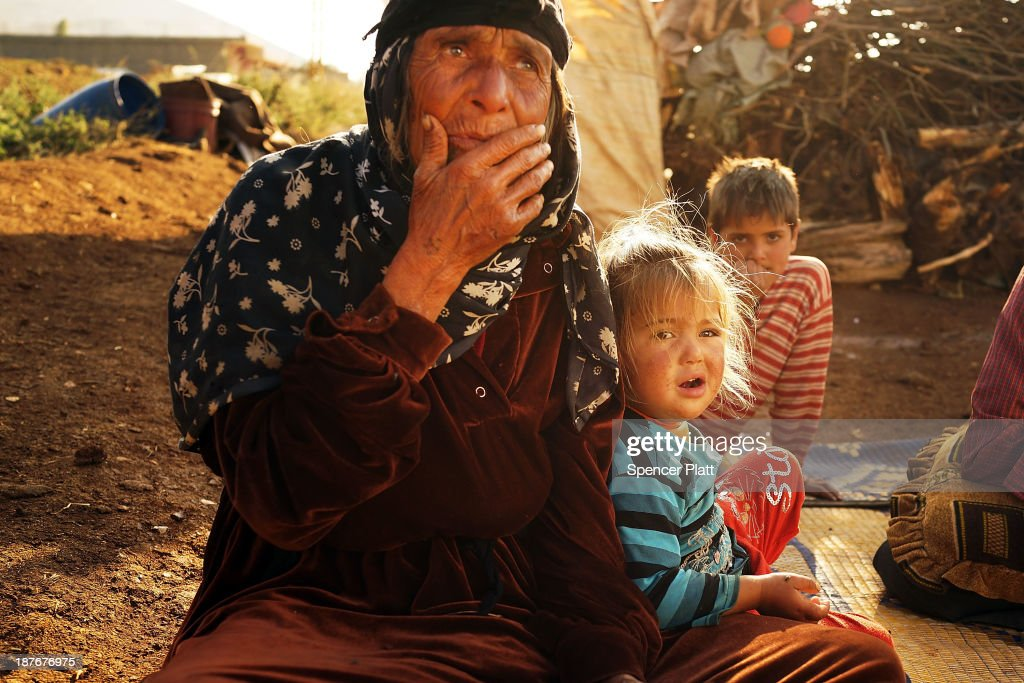 A woman and child who recently arrived from the besieged Syrian city of Aleppo pause in a makeshift camp in the Bekaa Valley, close to the border with Syria on November 11, 2013 in Majdal Anjar, Lebanon. As the war in neighboring Syria drags on for a third year, Lebanon, a country of only 4 million people, is now home to the largest number of Syrian refugees who have fled the conflict. The situation is beginning to put huge social and political strains on Lebanon as there is currently no end in sight to the war in Syria.