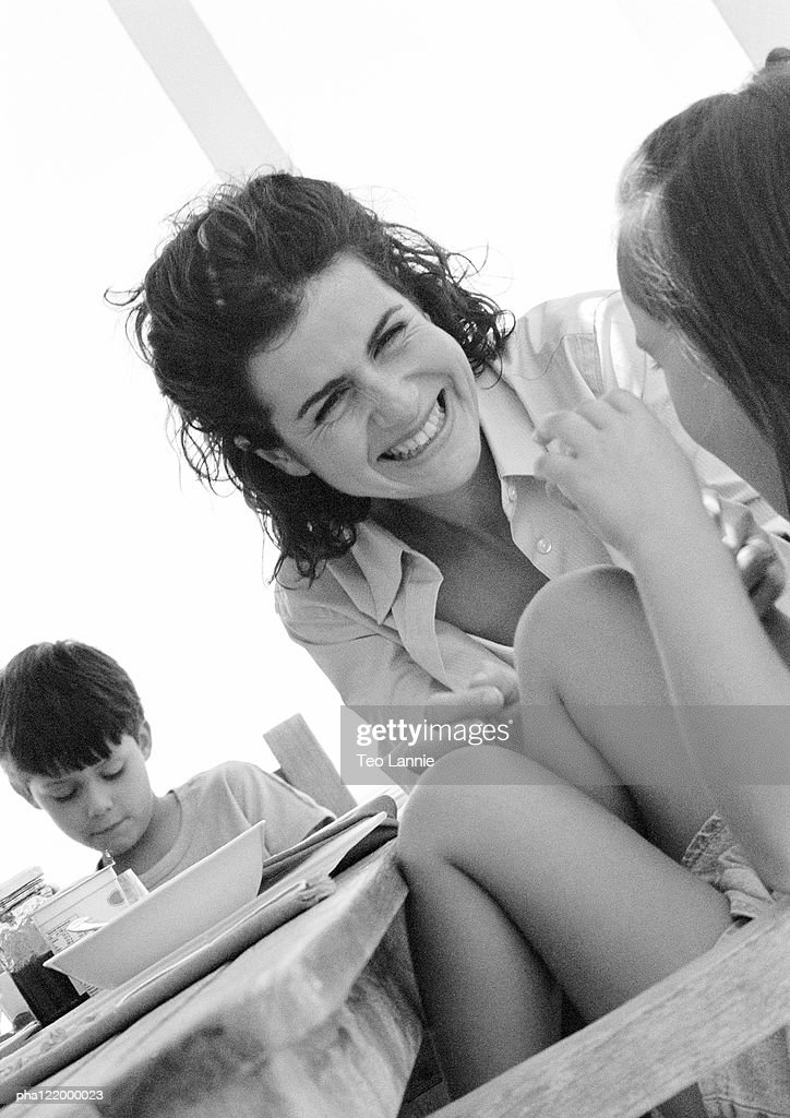 Woman and children at table, close-up, b&w : Stockfoto