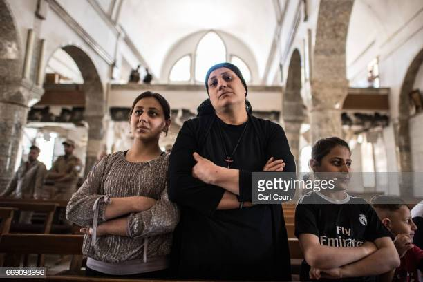 A woman and children attend an easter ceremony in Saint John's Church in the nearly deserted predominantly Christian Iraqi town of Qaraqosh on April...