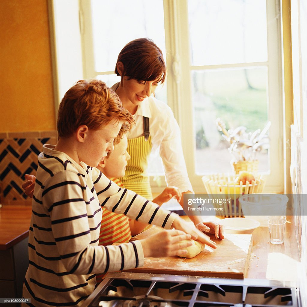 Woman and children cooking, side view : Stockfoto