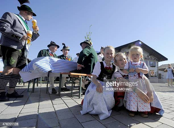 Woman and children dressed with Bavarian traditional regional costumes pose for the photographer before an event with US President and Germany's...