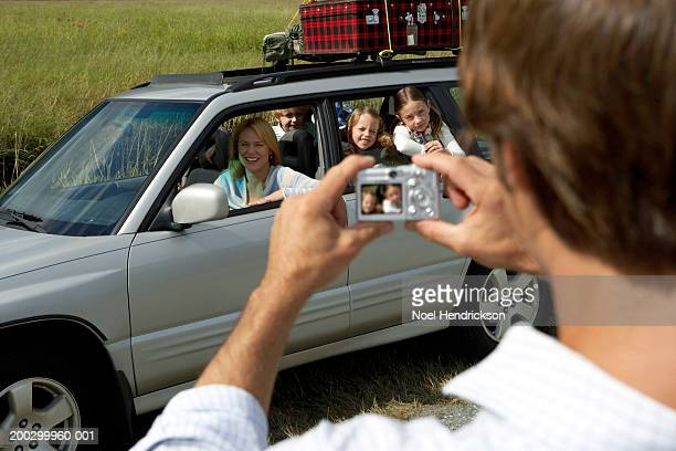 woman and children (6-8 years) in car being photographed by man, rear view, in foreground - 30 39 years stock-fotos und bilder