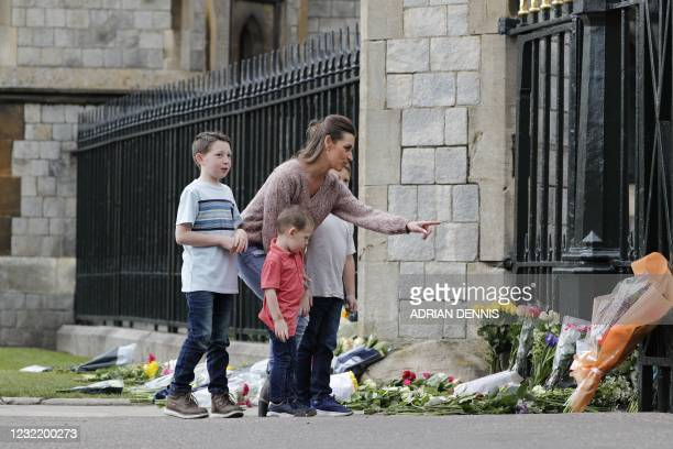 Woman and children pause at the floral tributes laid at the Cambridge Gate at Windsor Castle, in Windsor, west of London, on April 9 following the...