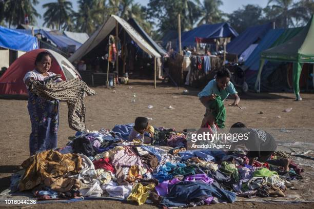 A woman and children pick clothes which are donated for people affected by earthquake at a temporary shelter in Lombok Indonesia on August 13 2018...