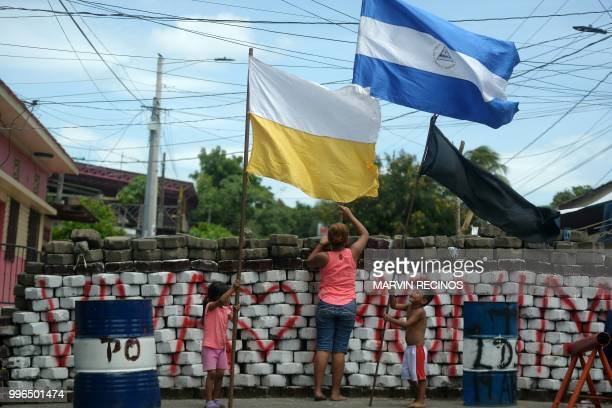 TOPSHOT A woman and children place a Nicaraguan a Vatican and a black flag on a barricade at Monimbo neighbourhood in Masaya Nicaragua on July 11...