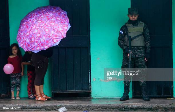 TOPSHOT A woman and children remain by a soldier at the Juan Guifarro Lopez school used as refuge during heavy rains in Tegucigalpa on October 7 2018...