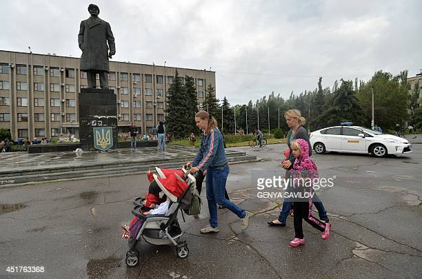 Woman and children, residents of the eastern Ukrainian city of Slavyansk walk past the city hall on July 6, 2014. Resurgent Ukrainian forces pursued...