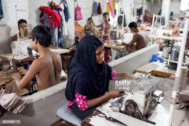 SADARGHAT DHAKA BANGLADESH woman and children sews a cloth in a local garment shop in Dhaka Bangladesh World Day Against Child Labor was observed on...