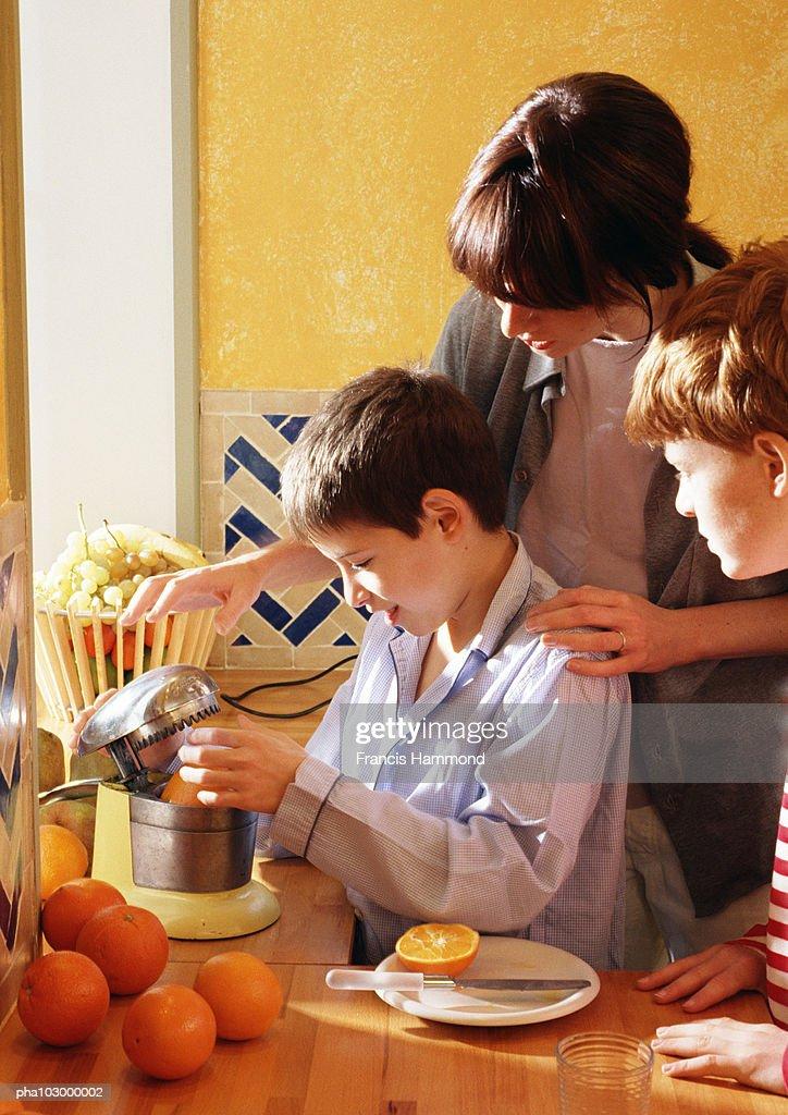 Woman and children squeezing oranges : Stockfoto