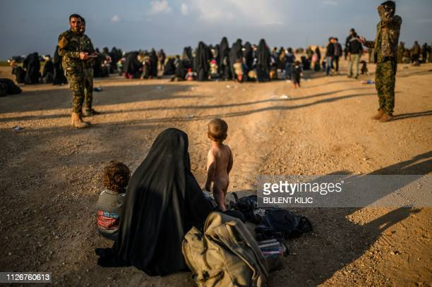A woman and children wait along with others to be searched by members of the Kurdishled Syrian Democratic Forces after fleeing the IS group's last...