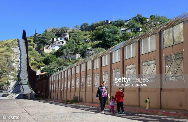 A woman and children walk beside the border wall and fence seperating the United States from Mexico on October 11 2016 in Nogales Arizona across the...