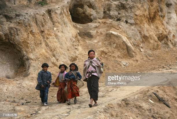 A woman and children walk on a mountain road on March 17 2006 in Panwa Kachin State Special Region 1 of Kachin State Myanmar The Kachin State Special...