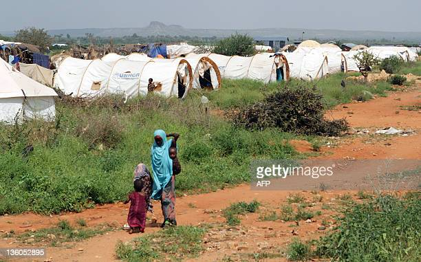 A woman and children walk through the Hilaweyn refugee camp in Dolo Ado Ethiopia on December 15 2011 Over 300000 refugees have fled severe drought...