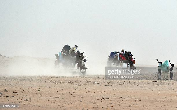 A woman and children wave to migrants sitting on pickup trucks holding wooden sticks tied to the vehicle to avoid falling from it as they leave the...