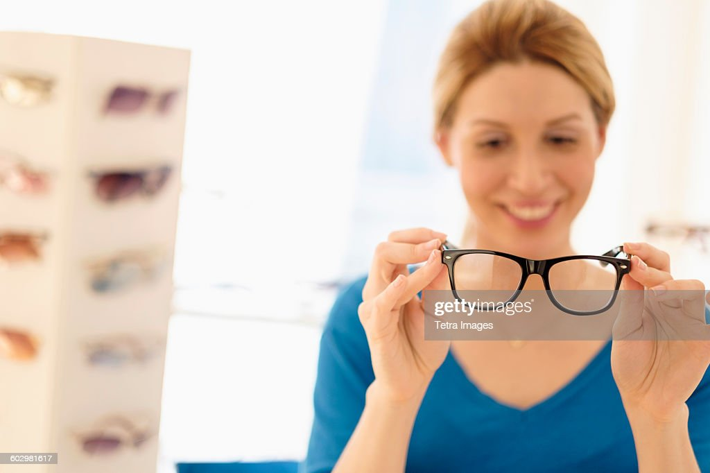 Woman and choosing eyeglasses in store : Stock Photo