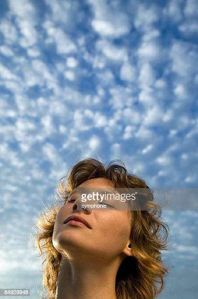 Woman and clouds in a blue sky