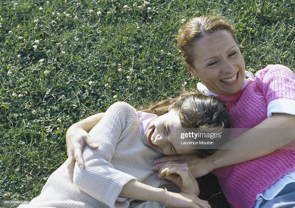 Woman and daughter lying on grass laughing : Stockfoto