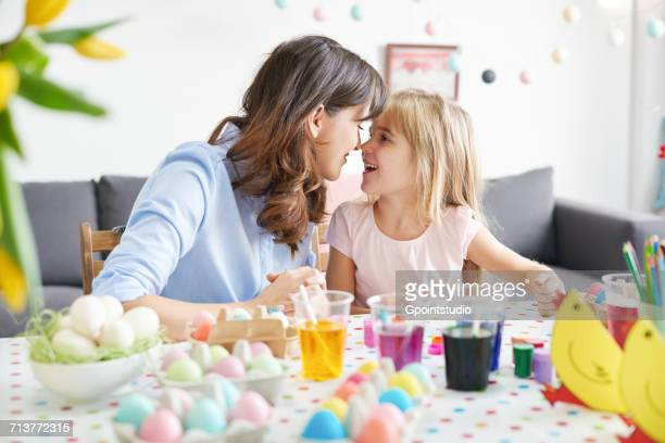 woman and daughter nose to nose while painting easter eggs at table - happy easter mom stock pictures, royalty-free photos & images