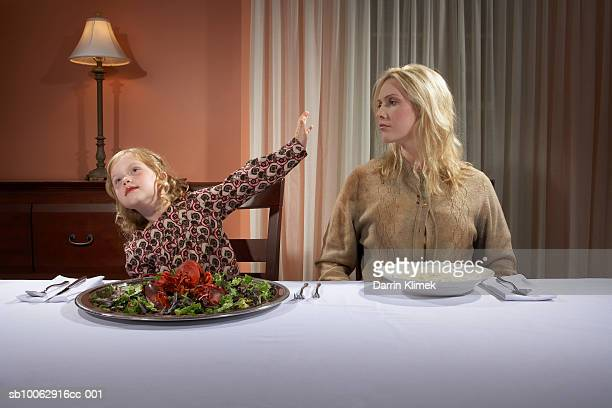 Woman and daughter (4-5) sitting at table in dining room, girl gesturing