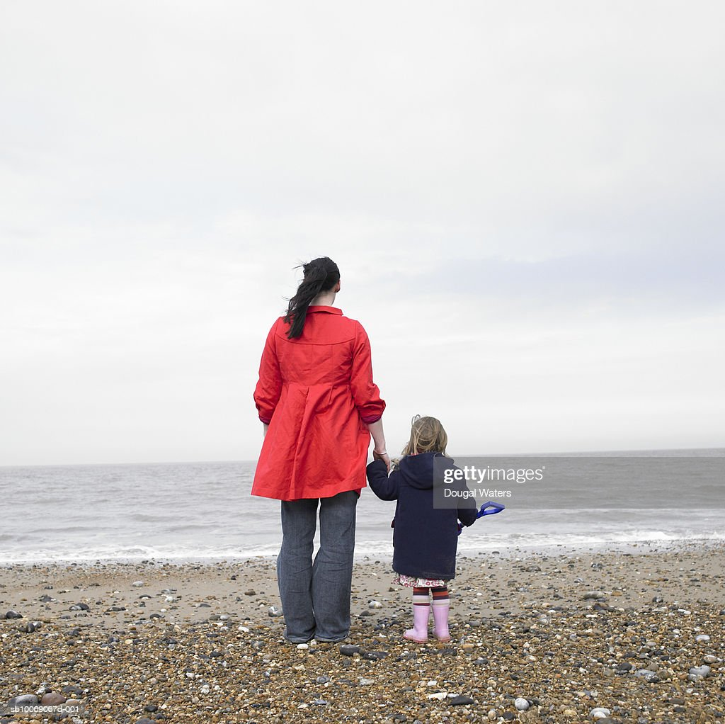 Woman and daughter (2-3) standing on beach, rear view : Stockfoto