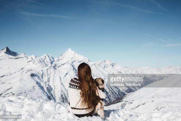 mulher e cachorro apreciando a vista dos alpes suíços de inverno - ski holiday - fotografias e filmes do acervo